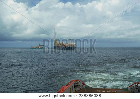 Anchor-handling Tug Supply Ahts Vessel During Dynamic Positioning Dpoperations Near Fpso Tanker. Ves