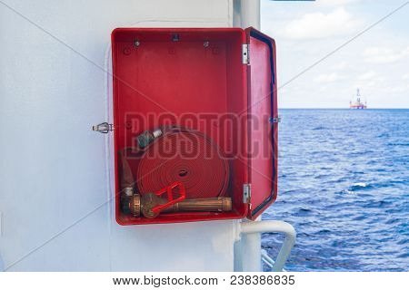 Fire Prevention Onboard Vessel At Sea. Fire Cabinet With Fire Equipment And International Fire Sign.