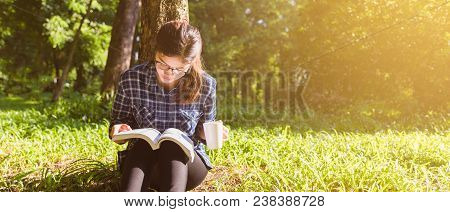 The Girl Sitting On A Green Grass With Cup Of Coffee And Reads The Book, Young Woman  With Coffee Si