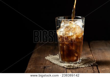 Ice Coffee In A Tall Glass Over And Coffee Beans On A Old Rustic Wooden Table. Cold Summer Drink On