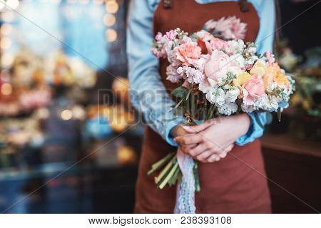 Young florist with a bouquet of flowers closeup