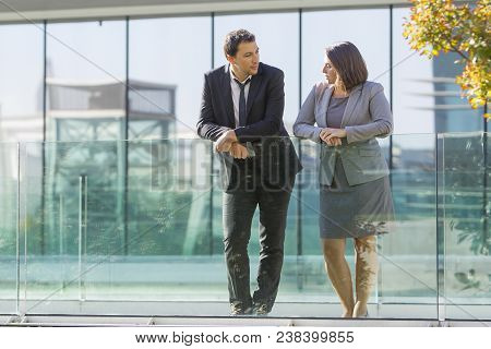 Serene Calm Business Colleagues Leaning On Glassy Railing While Resting Outdoors. Serious Confident