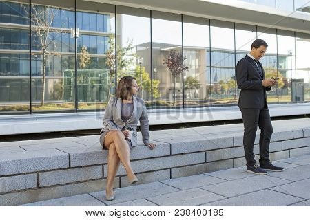 Pensive Pretty Business Lady Sitting On Slab While Handsome Male Manager Checking Message On Phone.