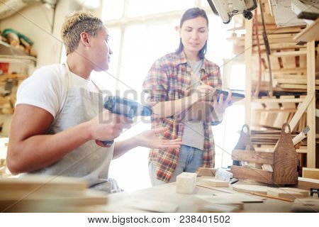 Young woodworker with drill talking to her colleague making notes or sketches in notepad