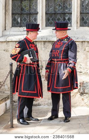 London, UK - 7th June 2017: Yeomans Guards, or Beefeaters, in conversation at the Tower of London. Formed in Tudor times, these guards have protected the monarch and Tower for over five centuries.