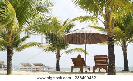 A Beautiful Girl In A Swimsuit Lies On A Lounger Under The Malmas. A Girl Is Resting By The Sea. The