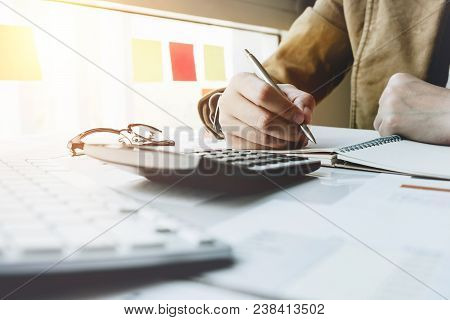 Close Up Woman Hand Using Calculator And Writing Make Note With Calculate About Cost Or Financial Fr