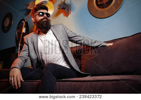 Brutal Bearded Man Sitting In Comfortable Sofa. Handsome Bearded Man In Suit On Luxurious Couch. Arr
