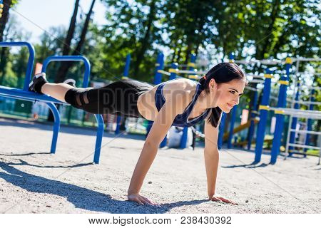 Young Sportive Female Trainer In A Bright Blue Sport Bra And Black Leggings Doing Push Ups On The Sp