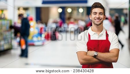 Shop owner arms crossed against blurry shops