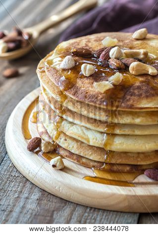 Stack Of Pancakes With Maple Syrup And Nuts