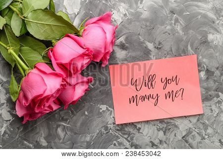 Pink Roses And A Pink Card With An Inscription, Will You Marry Me On A Gray Concrete Background. Con