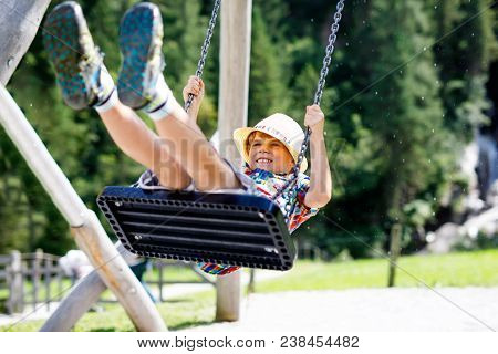 Funny Kid Boy Having Fun With Chain Swing On Outdoor Playground While Being Wet Splashed With Water.