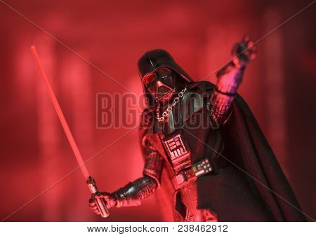 APR 26 2018: Star Wars Sith Lord Darth Vader reaching out to Force Choke while brandishing his lightsaber with red wash of light - Hasbro Black Series action figure