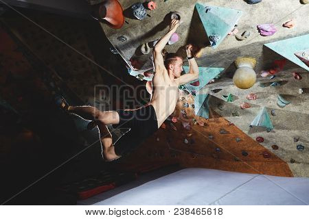 Workout Exercise. Top View Of A Man Climber Climbs Indoors In Bouldering Gym. Athletic Man Climbing
