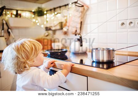 Toddler Boy In A Dangerous Situation At Home. Domestic Accident. Child Safety Concept.