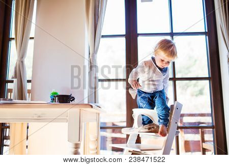 Unrecognizable Little Toddler Boy Climbing Into Wooden Highchair At Home. Domestic Accident. Dangero