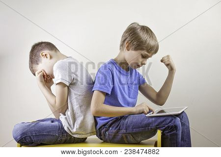Kids Playing Computer Games With Tablet Computer. One Boy Win The Game And Other Sitting Tired And U
