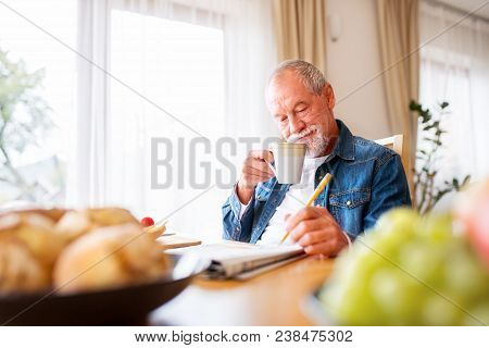 Senior Man Eating Breakfast And Doing Crosswords At Home. An Old Man Sitting At The Table, Relaxing.