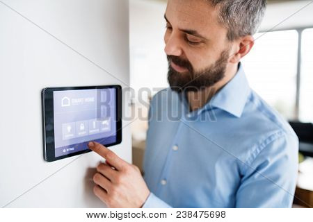 An Handsome Man Pointing To A Tablet With Smart Home Control System At Home.