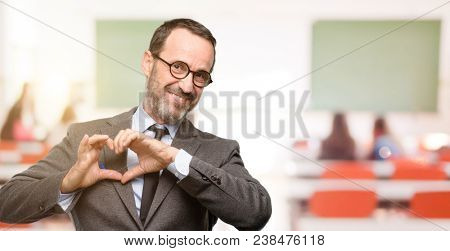 Teacher man using glasses happy showing love with hands in heart shape expressing healthy and marriage symbol at classroom