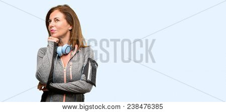 Middle age gym fit woman with workout headphones thinking and looking up expressing doubt and wonder isolated blue background