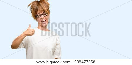 Crazy middle age woman wearing silly glasses smiling broadly showing thumbs up gesture to camera, expression of like and approval isolated blue background