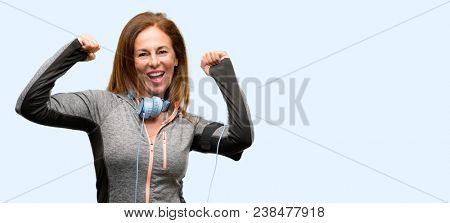 Middle age gym fit woman with workout headphones happy and excited celebrating victory expressing big success, power, energy and positive emotions. Celebrates new job joyful isolated blue background
