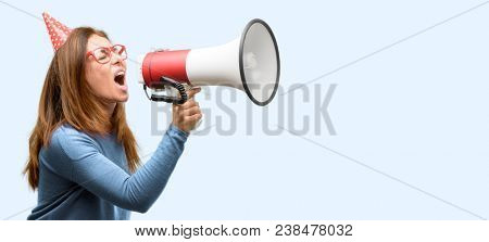 Middle age woman celebrates birthday communicates shouting loud holding a megaphone, expressing success and positive concept, idea for marketing or sales isolated blue background
