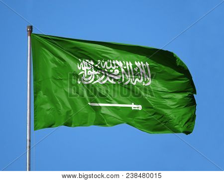 National Flag Of Saudi Arabia On A Flagpole In Front Of Blue Sky.