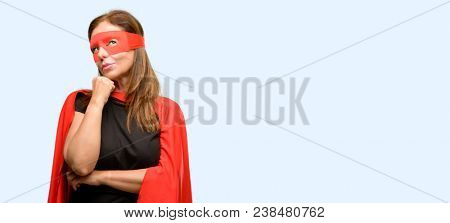 Middle age super hero woman wearing red mask and cape thinking and looking up expressing doubt and wonder isolated blue background