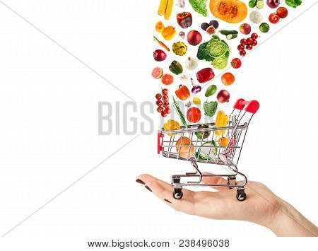Female Hand Holding Grocery Cart With Vegetables And Fruits Falling In It Isolated On White. Healthy