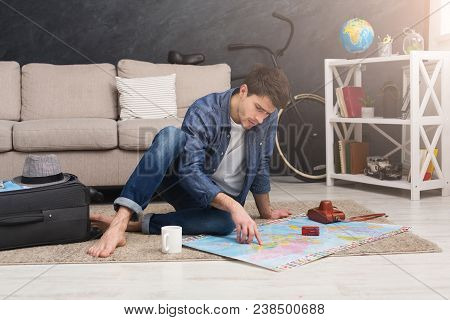 Young Serious Man Dreaming About Bus Travel Around World, Looking At Toy Bus On Map And Choosing Rou