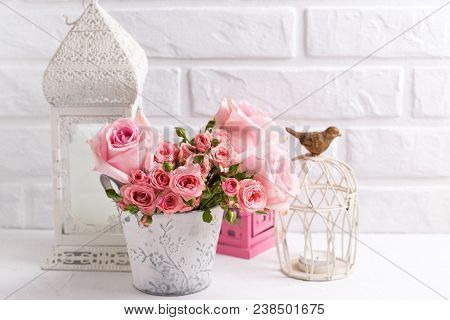 Pink Roses And Decorative  Lanterns  Against  White Brick Wall. Floral Still Life.  Selective Focus.