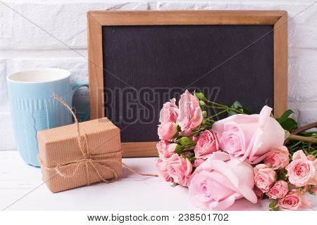 Pink Roses Flowers, Empty Blackboard,  Box With Present And Blue Cup On White Wooden Background. Flo
