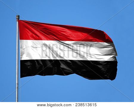 National Flag Of Yemen On A Flagpole In Front Of Blue Sky.