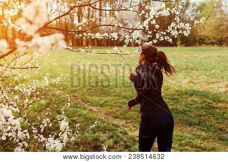 Happy Young Woman Running In Spring Forest Among Blooming Trees In The Morning. Helathy Lifestyle. M