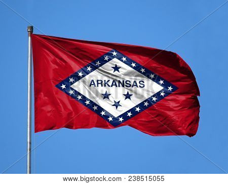 National Flag State Of Arkansas On A Flagpole In Front Of Blue Sky.