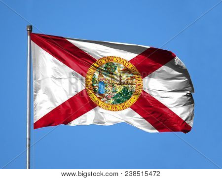 National Flag State Of Florida On A Flagpole In Front Of Blue Sky.