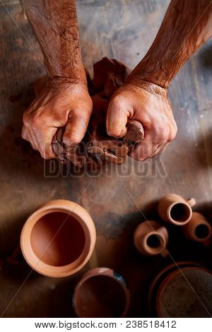 Adult Male Potter Master Modeling The Clay Plate On Potter's Wheel. Top View, Closeup, Hands Only.