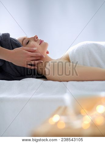 Young woman lying on a massage table,relaxing with eyes closed. Woman. Spa salon
