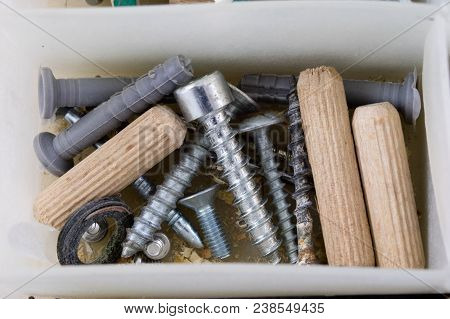 Wood Screws And Screws In A Plastic Workshop Container. Fitter Accessories In The Toolbox.
