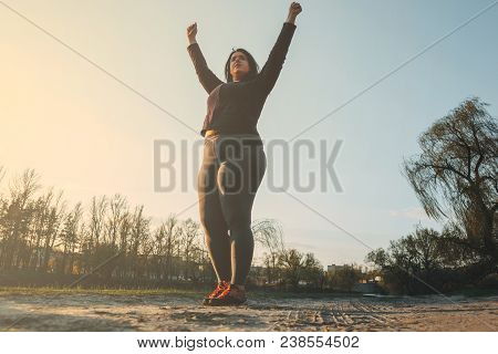 Happy Woman On Sunset Or Sunrise. Female Runner Raising Arms Expressing Positivity And Success.