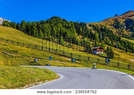 The road passes in the coniferous forests at the foot of limestone and dolomite rocks. Dolomite Alps. The beautiful sunny day. The concept of active, extreme and automobile tourism