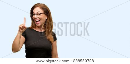 Middle age woman wearing black shirt and glasses pointing away side with finger isolated blue background