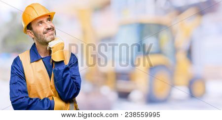 Senior engineer man, construction worker thinking and looking up expressing doubt and wonder at work