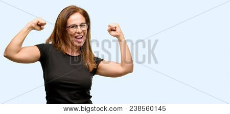 Middle age woman wearing black shirt and glasses happy and excited celebrating victory expressing big success, power, energy and positive emotions. Celebrates new job joyful isolated blue background