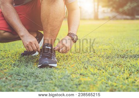 Close Up Man Tying Rope On His Sports Shoe. Preparing For Run In The Park In Sunset Time. Exercise A