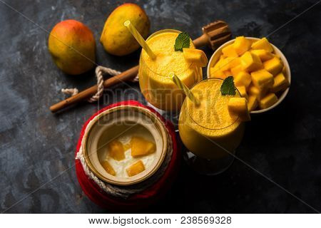 Mango Lassi Or Smoothie In Big Glass Or Small Bottles With Curd, Cut Fruit Pieces And Blender. Moody