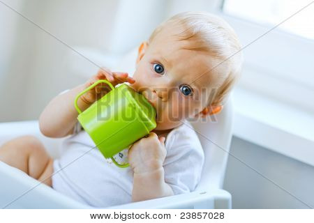Lovely baby sitting in chair and drinking from baby cup poster